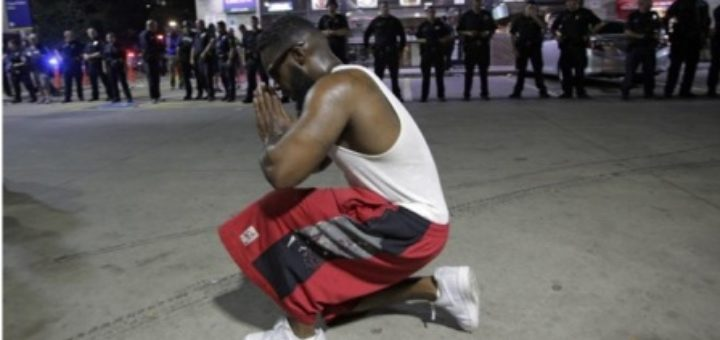 A protester prays near Dallas police after officers were shot during a protest in Dallas. (Credit: CNS/EPA.)