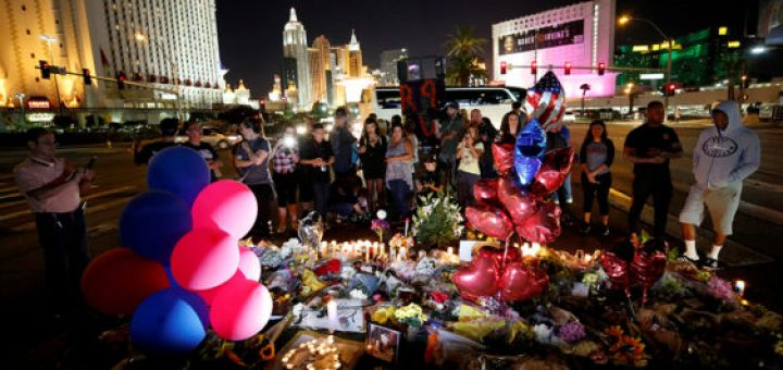 People gather at a makeshift memorial Oct. 4 for victims of a mass shooting along the Las Vegas Strip. A gunman, identified as Stephen Craig Paddock, 64, was perched in a room on the 32nd floor of a hotel and unleashed a shower of bullets on concertgoers below late Oct. 1. He killed at least 59 people and wounded more than 500, making it the deadliest mass shooting in modern U.S. history. (CNS photo/Chris Wattie, Reuters) See LAS-VEGAS-MASS-SHOOTING-PRAYERS Oct. 3, 2017.
